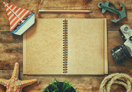 sailboat: top view image of open blank notebook, wooden sailboat, nautical rope and camera. travel and adventure concept. retro filtered image Stock Photo