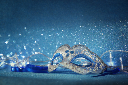 purim mask: blue female carnival mask and glitter background. with glitter overlay