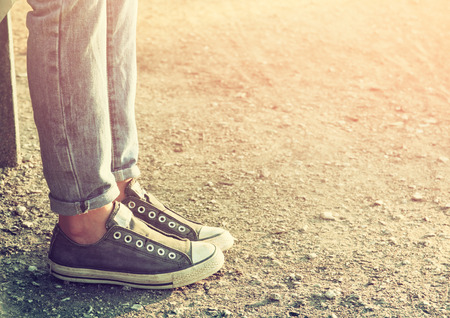 child feet: close up image of girl in sneakers sitting on the bench. Stock Photo