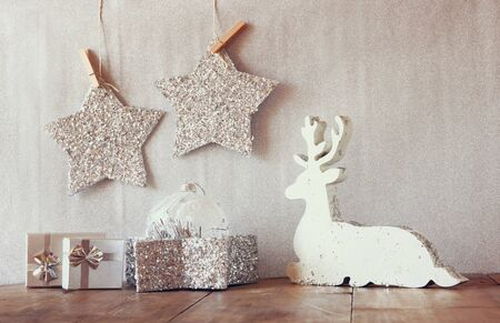 wooden reindeer: image of white wooden reindeer and glitter stars hanging on rope over glitter silver background. retro filtered with glitter overlay