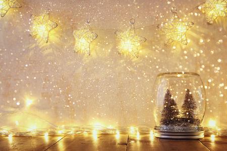 frasco: imagen de los árboles de navidad bajo llave y la vendimia se filtraron en frasco de vidrio con luces cálidas Garland y superposición de brillo. enfoque selectivo Foto de archivo