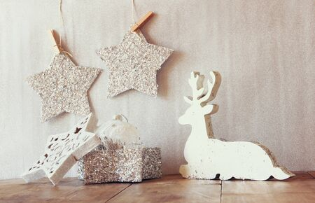 wooden reindeer: image of white wooden reindeer and glitter stars hanging on rope over glitter silver background