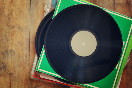 sixties: records stack with record on top over wooden table. vintage filtered Stock Photo