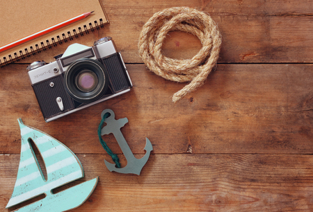 sailboat: top view image of notebook, wooden sailboat, nautical rope and camera. travel and adventure concept. retro filtered image