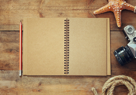 creative writer: top view image of open blank notebook, nautical rope, starfish and camera. travel and adventure concept. retro filtered image Stock Photo