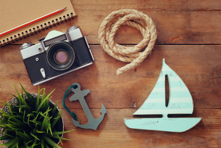 sailboat: top view image of blank notebook, wooden sailboat, nautical rope and camera. travel and adventure concept. retro filtered image