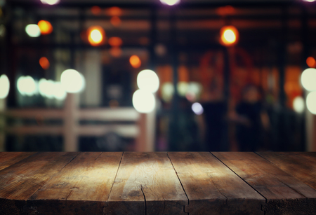 image of wooden table in front of abstract blurred background of restaurant lights