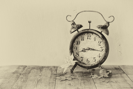 back in an hour: image of vintage alarm clock next to autumn leaves on wooden table in front of wooden background. old style photo