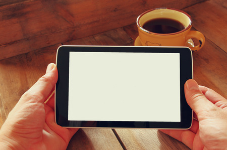 digital tablet: Digital tablet computer with isolated screen in male hands over wooden table background and cup of coffee