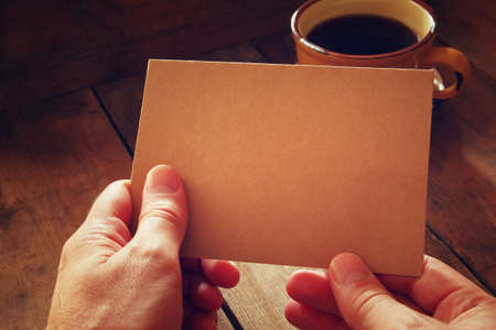 work table: male hands holding brown empty card over wooden table background and cup of coffee. retro style image, low key and warm tones