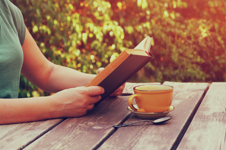 close up image: close up image of woman reading book outdoors, next to wooden table and coffe cup at afternoon. filtered image. filtered image. selective focus