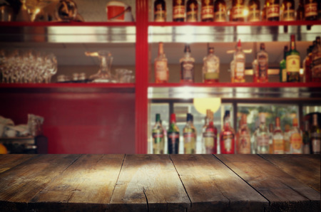 image of wooden table in front of abstract blurred background of resturant lights 스톡 콘텐츠