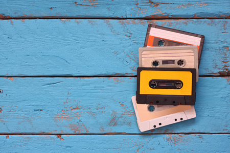 audio cassette: close up photo of vintage cassette tape over aqua wooden table . top view. retro filtered Stock Photo