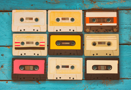 close up photo of vintage cassette tape over aqua wooden table . top view. retro filtered Archivio Fotografico