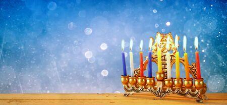 hanuka: website banner image of of jewish holiday Hanukkah with menorah traditional Candelabra. retro filtered. glitter overlay