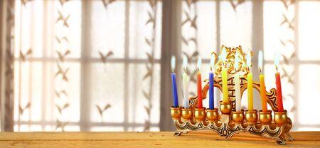menora: website banner image of of jewish holiday Hanukkah with menorah traditional Candelabra. retro filtered. glitter overlay