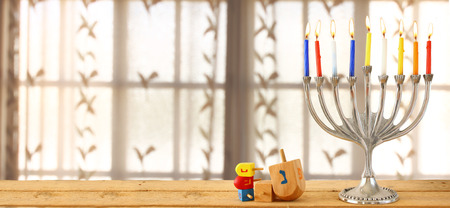 judaica: website banner image of of jewish holiday Hanukkah with menorah traditional Candelabra. retro filtered. glitter overlay