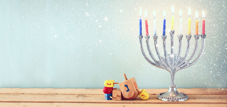 hanukiah: website banner image of of jewish holiday Hanukkah with menorah traditional Candelabra. retro filtered. glitter overlay