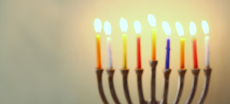 chanukiah: website banner image of of jewish holiday Hanukkah with menorah traditional Candelabra. retro filtered. glitter overlay
