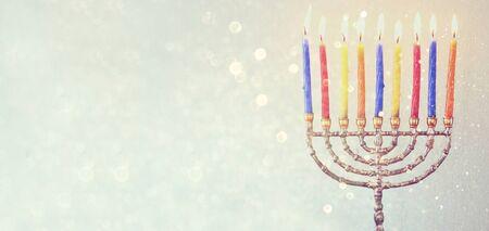 hanukka: website banner image of of jewish holiday Hanukkah with menorah traditional Candelabra. retro filtered. glitter overlay