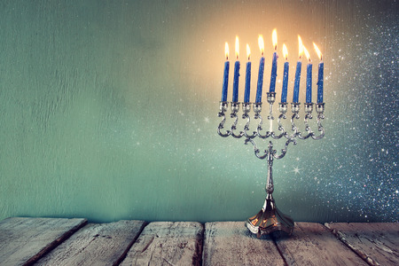 low key image of jewish holiday Hanukkah with menorah traditional Candelabra. filtered image