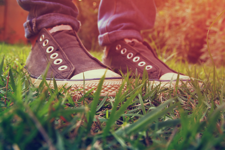 urban jungle: low angle photo of green grass and persons shoes. selective focus. retro filtered