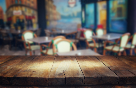 kitchen counter top: image of wooden table in front of abstract blurred background of restaurant lights