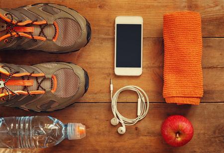 hombre deportista: concepto de fitness y calzado deportivo sobre fondo de madera .. visión superior