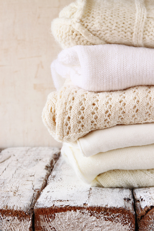 knit: Stack of white cozy knitted sweaters on a wooden table