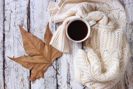 sueter: Imagen de la visión superior de blanco acogedora jersey de punto con a la taza de café y hojas de otoño en una mesa de madera.