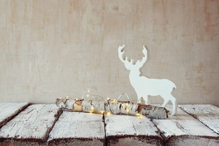 wooden reindeer: old tree log with fairy christmas lights and reindeer on wooden table.selective focus