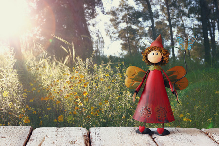 vintage landscape: cute fairy on wooden table in front of rural forest background