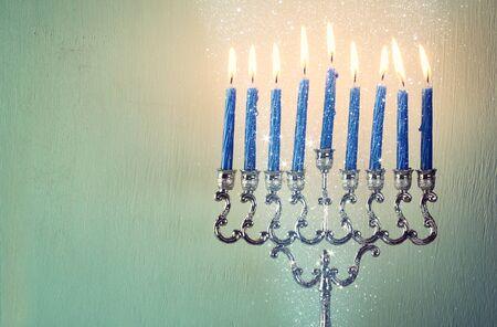 hanukka: low key image of jewish holiday Hanukkah with menorah traditional Candelabra. filtered image