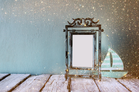 steel blue: low key image of old victorian steel blue blank frame with fairy garland lights and wooden sailing boat on wooden table. retro filtered image