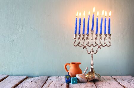 hanukah: image of jewish holiday Hanukkah with menorah traditional Candelabra and wooden dreidels spinning top