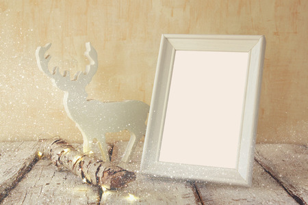 nature photography: image of old tree log with fairy christmas lights, reindeer and blank photo frame on wooden table.selective focus. template ready to put photography