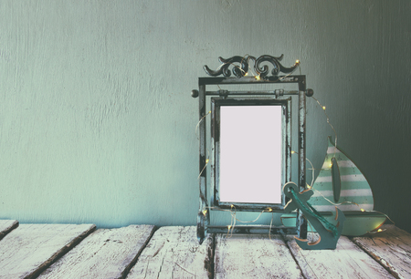 family vacation: low key image of old victorian steel blue blank frame with fairy garland lights and wooden sailing boat on wooden table. retro filtered image