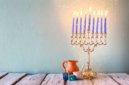 dreidels: low key image of jewish holiday Hanukkah with menorah traditional Candelabra and wooden dreidels spinning top