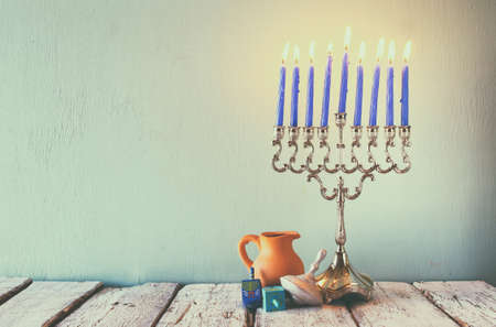hanuka: low key image of jewish holiday Hanukkah with menorah traditional Candelabra and wooden dreidels spinning top. faded retro filtered image Stock Photo