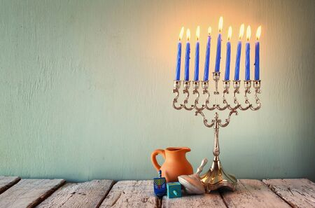dreidels: low key image of jewish holiday Hanukkah with menorah traditional Candelabra and wooden dreidels spinning top. faded retro filtered image Stock Photo