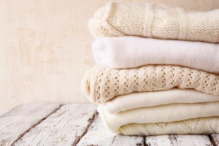 Pila de suéteres de punto blanco acogedoras en una mesa de madera Foto de archivo
