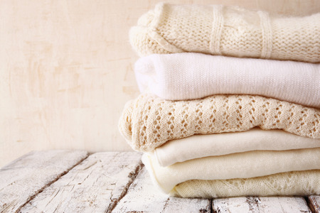 Stack of white cozy knitted sweaters on a wooden table