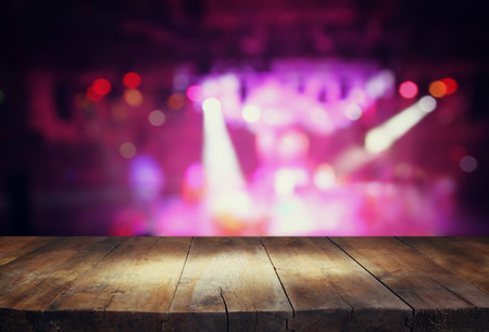 image of wooden table in front of abstract blurred background of stage lights