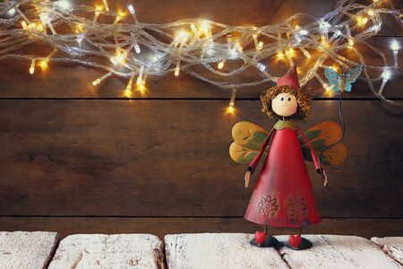 toy story: cute fairy on wooden table in front of garland gold lights background