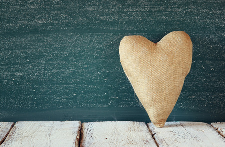 filters: image of vintage fabric heart on wooden table in front of blackboard