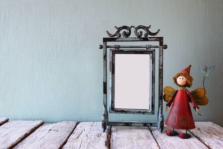 steel blue: low key image of old victorian steel blue blank frame and cute fairy on wooden table