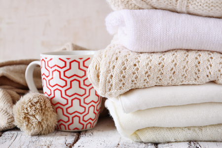 Stack of white cozy knitted sweaters next to cup of coffee on a wooden table Imagens