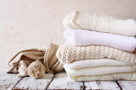 knitting: Stack of white cozy knitted sweaters on a wooden table