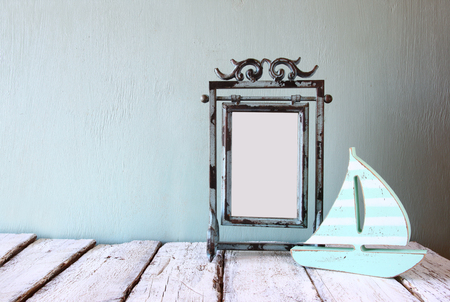 steel blue: image of old victorian steel blue blank frame and wooden sailing boat on wooden table Stock Photo