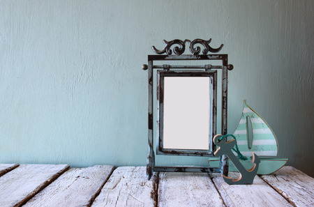 steel blue: low key image of old victorian steel blue blank frame and wooden sailing boat on wooden table